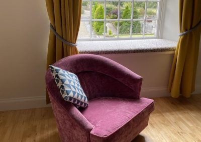 pink armchair by windowseat